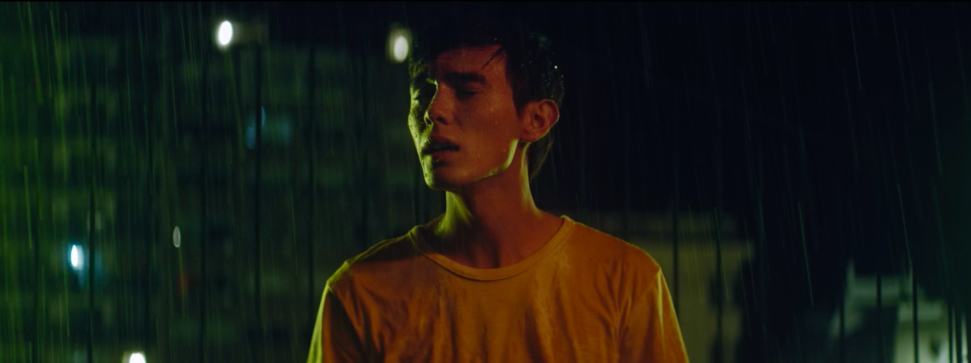 young man with eyes closed and a white tshirt stands in the middle of the street at night, under the rain