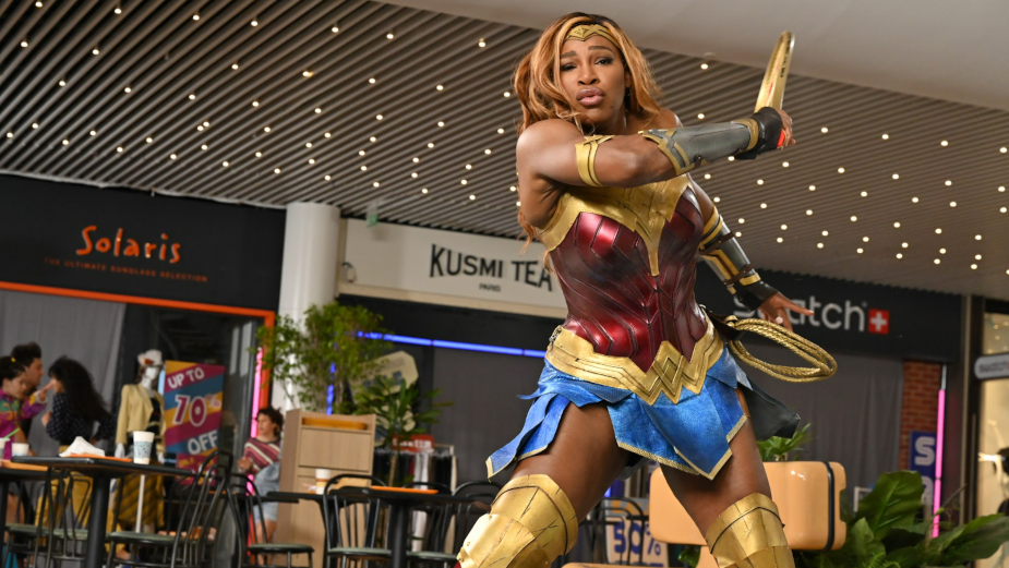 serena williams dressed as wonder woman playing tennis in a retro shopping mall