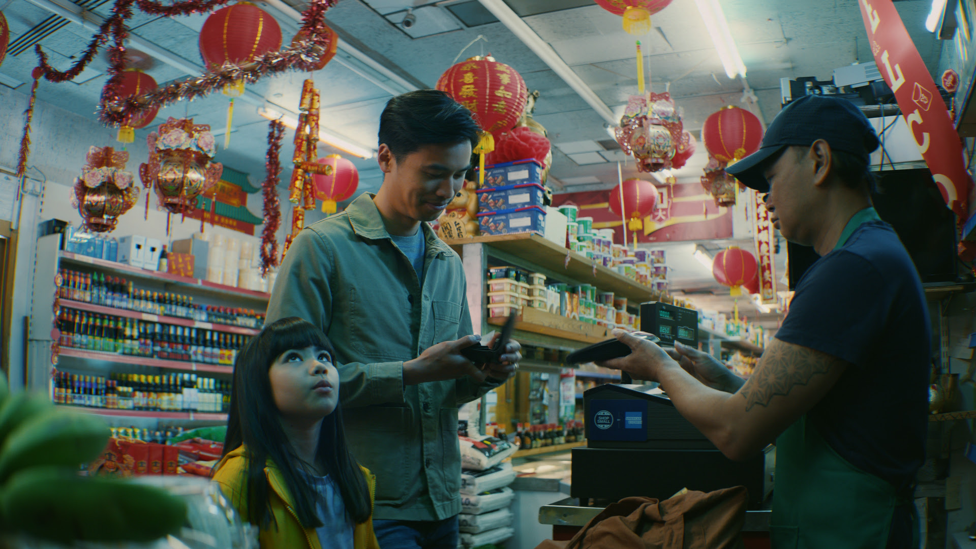 a man and his daughter are paying for an item in an asian grocery shop
